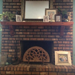 Fireplace - Antique carved stone architectural arch from India has a new life as a fireplace screen, standing in an iron bracket.