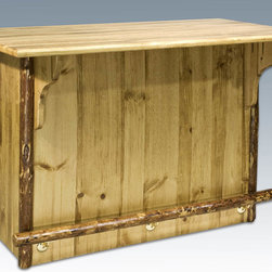 "Montana Woodworks - Glacier Country Bar with Foot Rail - Treat your friends to drinks at this rustic style bar with foot rail. The rustic beauty is sure to be a conversation starter extraordinaire! Handcrafted using solid, American grown wood this dry bar is designed for years of practical use while bringing a touch of the rustic into your home or cabin. The front features a log foot rail at the perfect height to be used with Montana Woodworks barstools. (Sold Separately) The back is open and features two storage spaces that can be used for bottles and all your bar accessories. Finished in the ""Glacier Country"" collection style for a truly unique, one-of-a-kind look reminiscent of the Grand Lodges of the Rockies, circa 1900. First we remove the outer bark while leaving the inner, cambium layer intact for texture and contrast. Then the finish is completed in an eight step, professional spraying process that applies stain and lacquer for a beautiful, long lasting finish. Comes fully assembled. 20-year limited warranty included at no additional charge. Hand Crafted in Montana U.S.A.; Solid, U.S. grown wood; Unique, one-of-a-kind Glacier Country style.; Heirloom Quality; 20 Year Limited Warranty; Durable Build, Fit and Finish; Each Piece Signed By The Artisan Who Makes It; Solid Wood, Edge Glued Panels; Barstool Height. Features Solid Lodge Pole Foot rail. Dimensions: 60""W x 29""D x 40""H"
