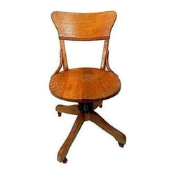 """Pre-owned 1900s Vintage Circular Oak Office Chair - A vintage wooden swivel office chair made in Milwaukee, WI. This chair has a very unique shape and is thought to be from the early 1900s. There is a small hairline crack on the seat.    Dimensions: Seat, 16.5""""Dia x 19""""H."""
