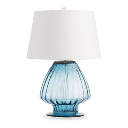 Herchel Lamp - There emanates from the Herchel Lamp a breezy aura like that found in the bungalows of Palm Beach, where blue water  prances with whitecaps and blue sky cavorts with clouds. The fluted glass lamp, delicately mouth blown, features an open base and closed top. The clear color of the blue seeded glass is made all the more striking when topped with the white microfiber euro taper shade.