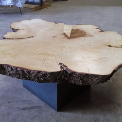 Coffee tables - This coffee table made from a round-ish section of a maple tree was a special request by one of our customers. The organic shape complemented by the cubic steel base was just what they were looking for in their living room.