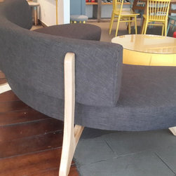 Moon shape sofa - This idea of sofa comes up with a western restaurant, the center of this restaurant space need something really invited the clients, make they want to seat on with group of friend. The legs of sofa make from Ash wood, thick canvas fabric. Comes up with this sofa we make color full round table and round stools.