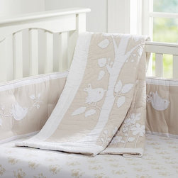 Sadie Nursery Bedding - Brimming with branches and sweet songbirds, this elegant bedding adds an artful softness to your baby's sleep space. Made of organic cotton percale with white bird and branch appliqués, the quilt features decorative stitching for the look of a hand-sewn original. A peaceful palette of khaki and cream lends the soft bumper its understated charm, and renderings of original watercolor designs give the sheeting a timeless feel.