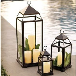 """Malta Lantern, Extra-Large, Bronze finish - Create a candlelight display with our handsome steel Malta Lantern year-round. Each lantern can rest on a flat surface or hang. Small: 5"""" square, 12"""" high; holds a 3 x 3"""" PB Pillar Candle. Candles are sold separately. Medium: 7"""" square, 18"""" high; holds a 3 x 6"""" PB Pillar Candle. Candles are sold separately. Large: 10"""" square, 29"""" high; holds 4 x 8"""" PB Pillar Candle. Candles are sold separately. X Large:  14"""" square, 40"""" high; holds multiple PB Piillar Candles.  Candles are sold separately. Substantially built of steel; with a bronze or silver finish. Thick glass panes."""