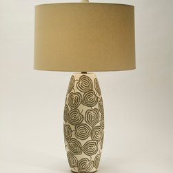 Relief Lamp - Leaf imprints dance along the oval base of the Relief Lamp, as if carried by a summer's breeze that lifts them high above a garden wall. The earthen tone color of the base serves as an understated background upon which the details of each leaf are intricately displayed. Topped with a shade of Linen Oatmeal, the lamp is a perfectly balanced fusion of functionality and earthly beauty.