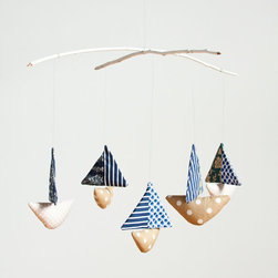 Baby Boat Mobile - Adorable little boats with spinning sails hang from white painted branches on this mobile from Made by Mosey. I love the patchwork details and softly stuffed shapes, and baby will too! Each piece is handmade by Melbourne-based artist Madeleine Sargent.