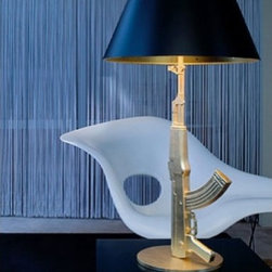 Flos - Flos Table Gun table lamp - The Table Gun is designed by Phillips Starck in 2005. Body is die cast aluminium with incection molded polymer overprint and gold platet finish. 18K. Matt black plasicized paper diffusor, silk screen gold plated inside.   Product description:     The Table Gun is designed by Phillips Starck in 2005. The body consists of die cast aluminium with injection molded polymer overprint and gold platet finish. 18K. Matt black plasticized paper diffuser, silk screen gold plated inside.  Lighting design is always pushing the boundaries to explore new ways and innovative ideas to bring light into our homes. One of the most controversial lamps to appear on the lighting scene in recent times is that of designer Philppe Starck's gun lamp. He is not the first designer to use contentious images to express himself and will not be the last either. First sight of these lamps provokes shock  with all that guns have come to stand for: violence, war and suffering, and disgust at having so powerful a symbol turned into a meek and mild domestic element. The pure gold plating on these gun lamps is just as powerful a symbol of greed and lust that seem to drive life to ever more irresponsible boundaries. There is an element of humour too at seeing a deadly weapon reduced to impotence and serving merely as a device to light up a room and perhaps that was Phillippe Starck's intention all along when he devised the idea of a gun lamp. The body of the Beretta hand gun lamp is produced from die cast aluminium with an injection moulded polymer overprint which is then finished with an eighteen carat gold leaf. On the top of the base is engraved the words - Happiness is a hot gun.... The shade is a matte black plasticized paper diffuser with printed inside in gold silk screen printing the signature Starck cross decoration. It accommodates a halogen bulb and operates with a dimmer cord. The gun lamps collection was first introduced as a prototype in the spring of 2005 