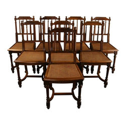 Used Antique French Dining Chairs Louis XVI - Set of 8 - This charming set of 8 French dining chairs dates to 1920, crafted in the timelessly sophisticated    Louis XVI style. The antique chairs are crafted in walnut wood featuring a very pretty patina of age. Tapered spindles on the seat back, fluted column legs and gently curved stretchers add the final touch of elegance to this set of dining chairs or side chairs. The cafe size chairs measure 36.5 inches high by 18 inches wide and 16.5 inches deep, with a seat height of 18 inches.    Overall Condition is Used - Good. Shows normal wear to the finish and miscellaneous nicks, dings, and scratches due to age and use. The side columns are slightly warped on two chairs. The cane is split at the edge on one seat and may need to be replaced.    Seat Height, Side Chair 18H .