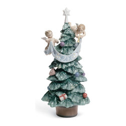 "Lladro Porcelain - Lladro Evergreen Of Peace Figurine - Plus One Year Accidental Breakage Replaceme - "" This is a traditional classic Christmas tree devoted to a message of peace, which is carried on a banner by two cherubs. The banner states the word PAX (Latin for Peace). On the tree there are also about eight ornamental balls in bright colours, plus a heart, a gift wrapped parcel, a treetopping star The tree is set on a wooden pot where the grains of the wood are to be seen thanks to the engraving of the porcelain.  Hand Made In Valencia Spain - Sculpted By: Joan Coderch - Included with this sculpture is replacement insurance against accidental breakage. The replacement insurance is valid for one year from the date of purchase and covers 100% of the cost to replace this sculpture (shipping not included). However once the sculpture retires or is no longer being made, the breakage coverage ends as the piece can no longer be replaced. """