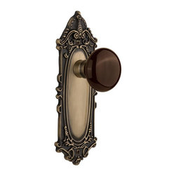 Nostalgic - Nostalgic Passage-Victorian Plate-Brown Porcelain Knob-Antique Brass (NW-710475) - The Victorian Plate in antique brass, with its distinct curvilinear embellishment, is unmistakably old world vogue. Adding our rich, Brown Porcelain knob only serves to compliment the warm, earthen hues in your home. All Nostalgic Warehouse knobs are mounted on a solid (not plated) forged brass base for durability and beauty.