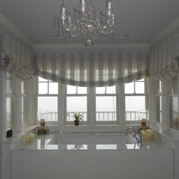 Bathrooms - A tub by the sea!  The client wanted the translucence of a sheer Belgian linen fabric to allow sunlight to filter into her very glamorous bathroom.  A voile fabric was used as a lining for durability.  The shades are working Romans that can be raised and lowered for privacy.
