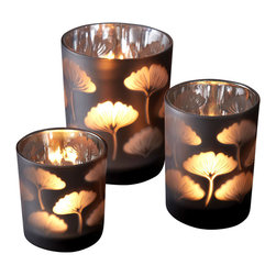 Gingko Leaf Glass Votive Candleholder - Set of 3 - Creating graceful glows and shadows, the Gingko Leaf Glass Votive Candleholders provide a warm, soft grey tone to the home's palette, but this delicate neutral contrasts with the fiery metallic silver of the inner lining. This set of three votive provides a floating botanical pattern for an all-season, soft-edged drama on a console, mantelpiece, or side table.