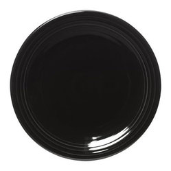 Fiesta Black Chop Plate 11.75 in. - Set of 4 - Dress up your modern table by using the Fiesta Black Chop Plate 11.75 in. - Set of 4 as a bold accent. Originally intended as platters for serving meats (such as chops, of course), chop plates are now often used as chargers at each place setting. These gleaming black plates would make the perfect backdrop for any style of china or any course of the meal. At 11.75 inches in diameter, they will peek out from behind your dinner plates for a luxurious look. Made from fully vitrified china with a lead- and cadmium-free glaze, each piece is microwave-, dishwasher-, and freezer-safe, and oven-safe up to 400 degrees Fahrenheit.About FiestaAmerica's favorite dinnerware line, Fiesta was introduced by the Homer Laughlin China Company in 1936 and quickly became a collector's item. Sets of Fiestaware are passed down from one generation to the next, as their Art Deco patterns have a timeless beauty, and their durable construction survives lifetimes of everyday use. Made from strong restaurant-quality ceramic with a rainbow of vibrant-colored lead- and cadmium-free glazes, and a full assortment of practical shapes, this line of kitchenware is easy to mix and match to create your own custom set. Fiestaware patterns have remained consistent throughout the years, although new pieces and colors are added, so modern cooks can customize and update their collection. Proudly made in America with a 5-year no-chip guarantee, each piece is microwave- and oven-safe, and dishwasher-safe for easy cleanup.