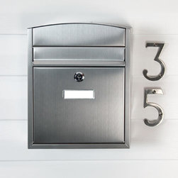 Compact Locking Wall-Mount Mailbox - Stainless Steel - The Compact Locking Wall-Mount Mailbox is sure to add a contemporary style to your home's entrance with its curved top and linear body. The stainless steel lid opens to reveal the mail slot and the locking feature will ensure the security of your mail.