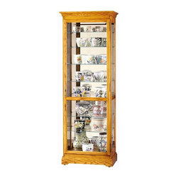 "Howard Miller - Chesterfield II Beveled Glass Curio Cabinet - Classic styling with eight unique extra deep glass shelf levels for your treasures, and an extra tall Golden Oak cabinet create an excellent decorative accent for any room. Beautiful features meet ultimate function with locking doors, adjustable levelers, and adjustable touch light offering four levels of illumination to enhance your collections. * This X-tra cabinet features extra deep shelves and extra height to accommodate your collectibles.. Beveled glass on the front door.. Finished in Golden Oak on select hardwoods and veneers.. Halogen lighting for brighter, whiter, longer-lasting light to illuminate your collectibles.. Adjustable levelers under each corner provide stability on uneven and carpeted floors.. Cabinet is illuminated by an interior light.. Locking door for added security.. Touch-Lite adjustable light switch offers four levels of lighting: low, medium, high, and off. A handy key holder is attached.. Eight levels of display space accommodate your many treasures.. Glass shelves can be adjusted to any level within your cabinet.. No-Reach light switch is conveniently located on the back of the cabinet.. Pad-Lock cushioned metal shelf clips increase stability and safety.. H. 78"" (198 cm). W. 28"" (71 cm). D. 17"" (43 cm)"