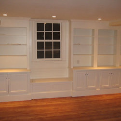 Belmont, MA Built-Ins - Here is a wall to wall custom built-in. The lower cabinetry is used for storage while the upper cabinetry is bookshelves. The unit also includes a neat little window seat. This unit is located in the downstairs family room. Whit Sprague