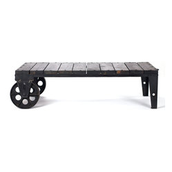 Peg Leg Rolling Factory Cart - Roll this into your living room for a distinctive coffee table. It makes a bold centerpiece to your room and can easily be moved around to fit changing seating arrangements. The cast iron wheels add a bit of vintage charm while complementing the rich dark table top. It gives your home just the right amount of industrial edge.
