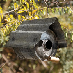 Galvanized Metal Repurposed Birdhouse - Flip an old metal jug on its side, toss the top and add a fluted metal roof. Voila! It's a low maintenance tract house for yard birds. Clever handle/perch.