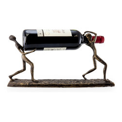 """Danya B - Two Men Carrying a Bottle Metal Wine Holder - Artistic cast iron wine holder shows two men carrying a bottle between them . Handcrafted and cast using the sand casting method. Bottom is lined to protect furniture. Great gift for the wine aficionado. Dimensions: 15"""" long x 8"""" high x 3.5"""" deep"""