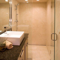 Space-Saving Curbless Shower Entry - This modern bathroom takes advantage of all available space with glass shower doors and beautiful tile work. The fact that the shower space is not interrupted by a drain helps make the space seem bigger while providing an accessible, curbless entry.
