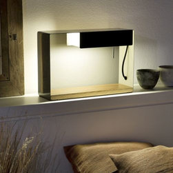 "Marset - La Discrete Table Lamp by Marset - Alternately employable as a lamp, light box or display shelf, the Marset la Discrete Table Lamp is inarguably one thing - an example of great design. A contemporary composition of lacquered metal and natural oak, the lamp is equally at home on a desk, table or console. When placed against a wall, it morphs into a portable back-lit shelf that would be ideal for highlighting a small piece of sculptural art. Marset is a Barcelona-based company dedicated to creating warm contemporary lighting with a underlying sense of comfort and character, enhancing otherwise impersonal residential and commercial spaces. The Marset mood is minimalist, subtle, with an aesthetic appeal that stems from an ""illuminate, not dazzle"" philosophy."