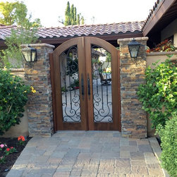 Casita Side Entry Gate - Custom built in a Mediterranean style with a segmented arch. Crafted using 2-1/4 inch old growth cedar for tighter grain.  Accented with gorgeous hand forged, powder coated Ironwork. - Chase Ford