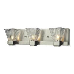 Three Light Brushed Nickel Clear Ribbed Glass Vanity - This spectacular three light vanity fixture consists of clear ribbed shades and is shown with a brushed nickel frame. This light, certain to stun its viewers, is also available with a chrome finish as well.