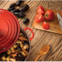 Le Creuset - Le Creuset Cherry Signature Round French Oven - LS2501-2267 - Shop for French Ovens from Hayneedle.com! The Le Creuset Cherry Signature Round French Oven makes a thoughtful gift for that budding gourmand or talented chef in your life. They'll be sure to appreciate its classic cast-iron construction and stunning red enamel exterior. Heat distributes evenly over the piece's bottom no matter the heating source (oven-rated up to 500 F; gas electric or induction stove safe). The heavy-duty no-slide lid helps to prevent boil-overs and keep moisture and pressure locked in with the dish. 3.5- 4.5- 5.5- 7.25- and 9-quart sizes are available. Pieces are dishwasher safe.About Le Creuset of America Inc.From its cast iron cookware to its teakettles and mugs Le Creuset is a global standard of inimitable color and quality. Founded in 1925 in the northern French town of Fresnoy-Le-Grand Le Creuset still produces enameled cast iron in its original foundry. Its signature color Flame was modeled after the intense orange hue of molten cast iron within a cauldron (or creuset in French) and has been a Le Creuset bestseller from the company's first year to the present day.Though best known for its vibrantly colored cookware and original inventions such as the Dutch oven Le Creuset has also forged a name as a creator of stoneware mugs and enamel-coated stainless steel teakettles. The style and performance of Le Creuset's Cafe Collection and tea accessories are rooted in classic French cookware: bold colors cylindrical loop handles unmatched thermal resistance and heat distribution and of course the iconic Le Creuset three-ring accent. Through its consistent qualities of authenticity originality and innovation Le Creuset maintains a connection to both heritage and modernity.