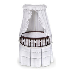 Badger Basket - Badger Basket Elite Oval Bassinet - 00856 - Shop for Bassinets and Parts from Hayneedle.com! Let Baby sleep in stylish comfort. The Badger Basket Elite Oval Bassinet is the perfect solution to your nursery furniture needs and gives you a decorative look along with total peace of mind when it comes to your little one. Made from wood wood composites and powder-coated steel the body of the bassinet has an upscale oval shape complete with height-adjustable overhead canopy. No more harsh ceiling lighting waking up Baby - the enclosed area inside is an invitation to hours of peaceful sleep.A delicate dark wood cherry finish on the bassinet matches the included bedding for a gender-neutral look that matches any nursery you've created. Included are a mattress (approximately 1-inch thick) foam vinyl-covered mattress pad skirt bumpers and fitted sheet all in white. The bumpers attach to the bassinet with grip tape and ribbon ties and are padded with polyester fill. The sheet is 80% polyester/20% cotton and the rest of the bedding is 100% polyester; all items are machine wash cold and tumble dry low.The interior of the Elite measures 29.5L x 21.5W x 7.5H inches. It features caster wheels for easy transport. A storage shelf beneath the bassinet is perfect for storing necessities. Overall the bassinet measures 32L x 25W x 53.5H inches; from the top rim to the floor it stands 29.5 inches (20.5 inches from the lower rim to the floor).This bassinet is for use up to 20 pounds 3-4 months or until Baby can roll over push up or sit unassisted. Assembly required.Badger Basket CompanyFor over 65 years Badger Basket Company has been a premier manufacturer of baskets bassinets bassinet bedding changing tables doll furniture hampers toy boxes and more for infants babies and children. Badger Basket Company creates beautiful and comfortable products that are continually updated and refreshed bringing you exciting new styles and fashions that complement the nostalgic and tradit