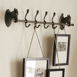 "Horse Row of Hooks, Bronze finish - Five hooks held by cast-iron horses bring equestrian chic to the task of organizing at home. Each hook is topped with a ball finial to double the storage capacity for hats, coats, leashes and more. 39"" wide x 4.5"" deep x 6.5"" high Made of cast iron with a rustic bronze finish; lacquer sealant. Catalog / Internet only."