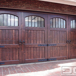 Dynamic Garage Door - California Dream 14   Spanish Architectural Garage Door With Iron Hardware - Knotty Alder Custom Garage Doors yield a variant display of color, grain and knots that undoubtedly are natural features that only this species of wood does so well. Heavy ring knockers, beefy iron hinges and iron spindle window inserts make up the various features of this custom garage door. The antique seedy glass gives this door a touch of ageless beauty and rustic appeal. Together, all these elements complete this two car garage door that may look like for individual swinging doors if you don't look closely.