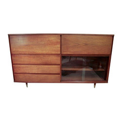 Pre-owned Large Mid-Century Bar, Desk & Storage Credenza - Storage, style - this large and unusual credenza has it all! It includes three storage drawers, two pull down front doors that reveal a bar with the original 16 glasses, and a desk and storage drawer. The credenza also has a front storage area with one shelf behind two original glass sliding doors. The wood appears to be walnut and the legs are capped in brass.    The interior cabinetry is also electrified. The right area lights up and has the original mirrored back. The wiring is original and needs replacement. It's in good vintage condition with minor surface wear to the wood, but no maker's mark.