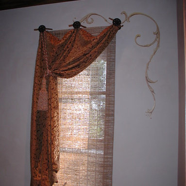 Custom Draperies - Tie top pleated fabric attached to deco medallions with ties and mounted over a woven wood shade. Tied back  with a tassel tie to frame the window.