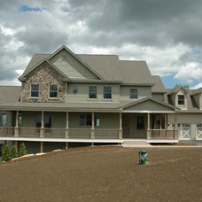 Farmhouse Exterior by TARKKA HOMES INC