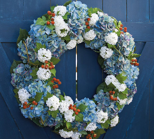 Frontgate - Americana Wreath - Faux flowers, artistically arranged. Suitable for indoor and sheltered outdoor use. Arrives ready to hang. Durable and maintenance free. Dust with a dry cloth. Show your patriotic spirit in a more subtle and elegant way. Our all-season Americana Wreath brims with bouquets of Blue mophead hydrangeas, clusters of white Annabelle hydrangeas, and wild red raspberries.  .  .  .  .  . Imported.