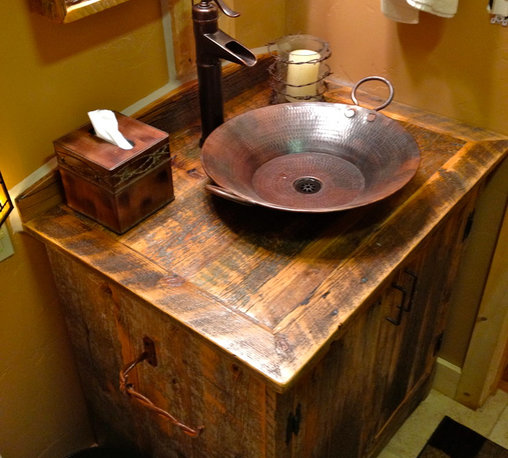 Rustic Furniture Portfolio - Custom vanity with a hand hammered copper vessel sink and well faucet.  Reclaimed barbed wired and barn wood mirror matches the piece.