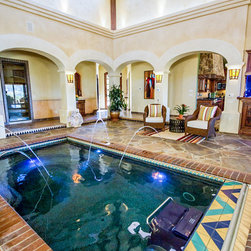 Fastlane by Endless Pools - A stunning foyer with exposed beams, arched doorways, and showpiece water features.