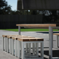 Vigor - An eye striking set with charisma to spare. The rough Teak or Mahogany beams are jointed to the aluminum frame by obvious dovetail shaped strips, replicated in the matching bench and stools. A very old technical solution, that proves today to work aesthetically as well! The picnic-set taken to an unseen level!