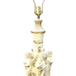 "Consigned Gold Gilt White Italian Ceramic Putti Cherub Lamp - An exquisite antique Italian ceramic table lamp. The lamp features a gold gilt finish over white Italian ceramic with 4 putti cherubs adorning the base. The height base to top of sculpture: 21"" height to top of lampshade screw: 31.5"" base width: 9.75"" height of cherubs bottom of feet to top of head : 8.75"" weight: 10lbs. Antique Vintage Gold Gilt Art Deco White Italian Ceramic 4 Putti Cherub Large Lamp"