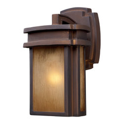 ELK - ELK 42146/1 Outdoor Sconce - Simplicity Of Craft And Form Gives The Sedona Collection A Very Attractive Look Through Its Minimalist Approach.  Inspired By The Architecture And Casual Lifestyle Of The Desert Southwest, This Collection Features Clean Lines With Recessed Edges, Caramel Beige Glass, And A Clay Bronze Finish.