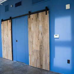 Sliding Barn Door - Mixed Natural Hardwood - Here are a couple sliding barn doors we installed for a customer in Central Phoenix, AZ.  The doors are made out of a mixture of natural unfinished reclaimed hardwoods.  The customer decided that the sliding barn doors would look great unfinished, allowing the texture of the natural reclaimed wood to stand out accenting the bright blue walls.  We used Rustica hardware to install the door, maintaining the modern industrial look.