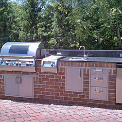 Fire Magic Outdoor Kitchen - Masonry Outdoor Kitchen with Fire Magic Equipment. Fire Magic Echelon Diamond with Magic View Window, Echelon Diamond Searing Station, Premium Refrigerator, Kegerator, Flush Mounted Access Doors & Drawers. Granite countertop with back splash.