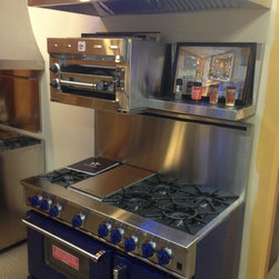 Babylon Showroom - This is a picture of our new addition to the showroom. It is a custome colored Bluestar range with a Salamander on the backguard and a matching stainless steel hood. Some serious cooking power! This range is price from $7,999 to $11,999 based on the configuration.