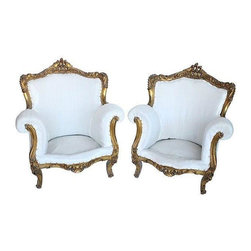 """Used Antique French Gilt Bergere Chairs - A Pair - Pair of French bergères with ornate gilt frames, rolled arms, and nailhead trim. This pair has been stripped of the dated upholstery and recovered in a white muslin undercoat ready for your choice of fabric or to leave as is. Made in France. Seat measures 20.5""""W x 13""""H."""