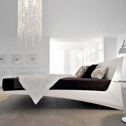 Cattelan Italia - Cattelan Italia | Dylan Bed - Made in Italy by Cattelan Italia.Exuding a look and feel of elegance, the luxurious Dylan Bed is the epitome of Catellan Italia's fashion-forward design philosophy. Appearing to be cantilevered and afloat, this large showpiece bed features clean geometrical lines and angles and will give a sense of lightness and serenity to any formal or master bedroom. Soft premium leather upholstery embraces the bed's wide rectangular headboard and solid timber frame, which is discreetly propped up by four equally stylish steel feet in a sleek finish. The piece comes with timber slats to support a mattress (not included). Choose from a range of leather colors and textures. Comfortably sleeps two.