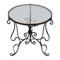 Used Iron Glass Top Side Table - This lovely iron table has a glass top that measures 19.5 inches in diameter. The floral bouquet beneath the glass has painted flowers that are supported by delicately scrolled legs. The edge of the piece is embossed with a garland surrounding the glass. This table could work either inside or out accenting any decor.