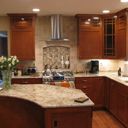 The Range Hood is the Centerpiece of the Kitchen - Here we installed a direct vent hood leaving the wall behind open. We continued the back splash tile to the ceiling creating an open look to the kitchen.  The recessed niche completes the effect.