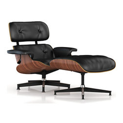 Herman Miller - Eames Lounge Chair and Ottoman, Walnut Frame/Black Standard Leather - The Eames Lounge Chair and matching ottoman looks simply stunning with the Herman Miller Walnut frame and black leather. Perfect for the home or as a place of retreat in the office- the Eames Lounge Chair is a low recliner that attracts the eye and it could not be more inviting. Charles and Ray Eames designed the chair and it is mentioned whenever designers point out icons of the mid-centry furniture design movement. Wherever you decide to put it this Eames chair will fit right in and be a favorite for years. Since it was released in 1956 it has been the gold standard of designer furniture chairs. It is display at the Museum of Modern Art as one of the permanent exhibits. The Eames Lounge Chair and Ottoman is made of 24 percent recycled materials. Herman Miller has long been a steward of the environment and has done an impressive job of combining high industry with environmental responsibility. A significant portion of the chair and ottoman are recyclable but you won't be recycling it anytime soon because it will last for years if not decades.