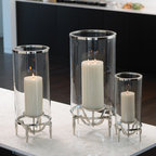 Elevated Hurricane- Medium - A pillar candle sits neatly in a deliciously complex architectural support, shielded by a cylinder of nickel-rimmed clear glass, in the Elevated Hurricane tabletop candle holder.� Constructed with four dramatically-angled legs that join to raise the candle on a sleek metal cup, this hurricane lantern is a neat and polished indoor element that looks elegant in your decor whether the candle is lit or not.� Place in a row with the larger and smaller versions for a glamorous effect.