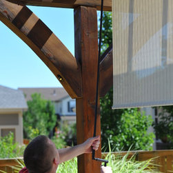 Exterior Solar Screen Shades With Crank Control - customer lowering patio shade that features our titanium pole and crank control. Perfect for child or pet safety.